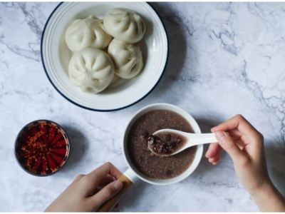 A photo shows a plate of four dumplings, a bowl of clear soup, and a pot of hot sauce on a table. A human hand holds the soup bowl with left hand and takes of soup with a soup spoon.